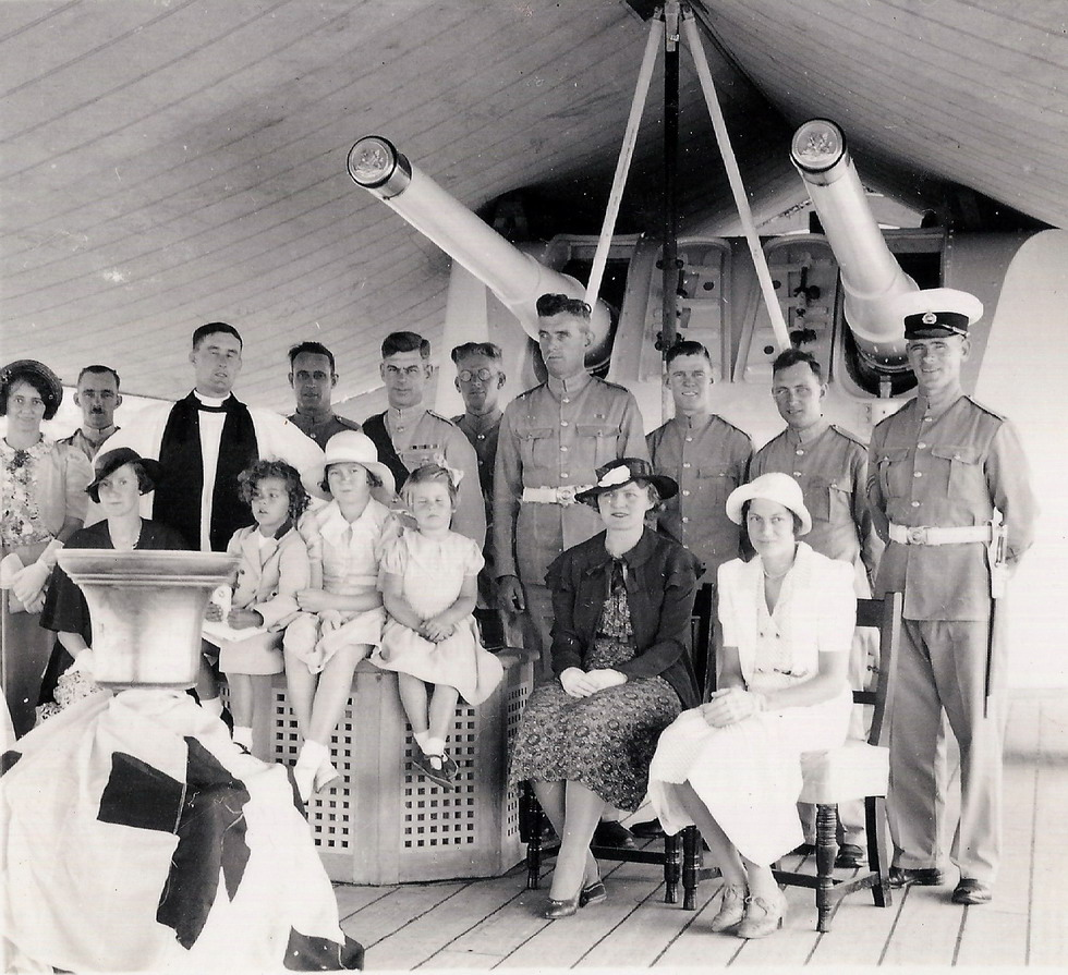In the centre is John's father, Colour Sergeant Norman Dallen, Sergeant Major of the Garrison in his distinctive red sash.\n The curly little girl sitting up on the bollard cover in front of the Chaplain is John's five year old sister Norma. The tall Marine just to the right is Gerry Saunders and his wife is the lady in the pretty white dress.
